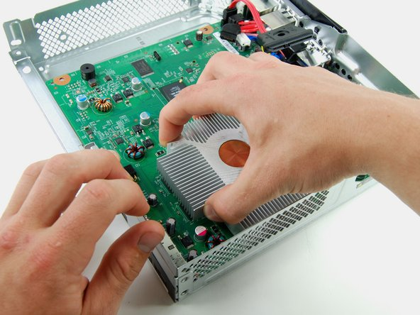 Grab the heat sink with one hand, and hold the metal frame with the other.