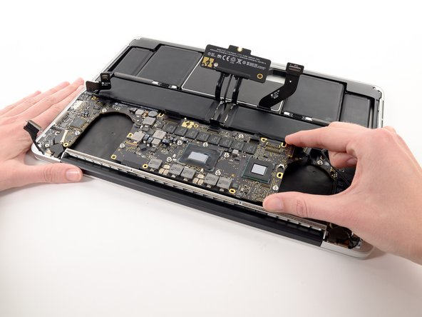 Carefully grasp the corner of the logic board (opposite of the I/O ports) and lift the logic board out of the upper case.