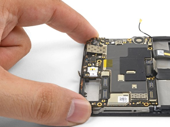 Use your fingers to lift up the top edge of the motherboard.
