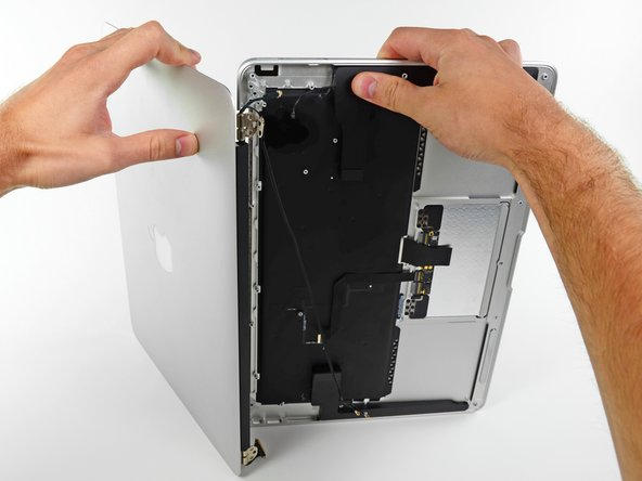 Push the upper case slightly toward the display assembly, then rotate it away from the front of the display assembly.