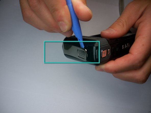Use a small plastic pry tool to gently pry off the silver strip on the top of the camera.