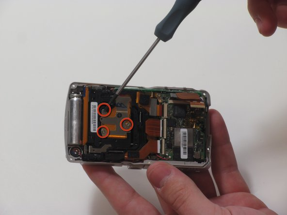 Using a size 0 Phillips head, remove 3 screws holding the ribbon cable that covers the back of the lens.