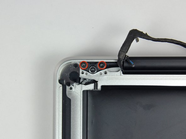 Remove the two outer T8 Torx screws securing each side of the display bracket to the upper case (4 screws total).