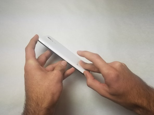 Remove the backplate. It's possible to use your fingernail, but the edge of your finger should work as well.