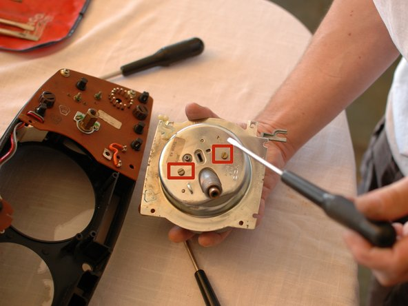 Now you can remove the two flat head screws that hold the metal back on the speedometer assembly.