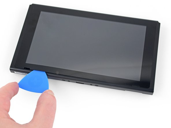 Slide the opening pick along the bottom edge of the screen to slice the adhesive.