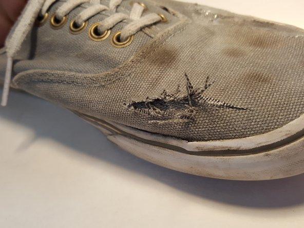 Schneide an der zu reparierenden Stelle mit einer Schere alle losen Fäden und überstehende Teile des Materials ab.