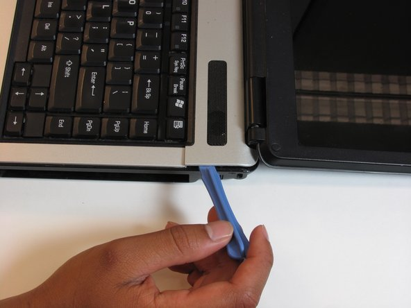 Using the plastic opening tool, pry off the panel above the keyboard, starting near the right front speaker.