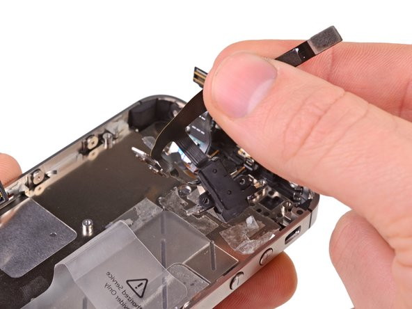 Carefully peel the headphone jack/volume button cables off the adhesive securing them to the rear case.