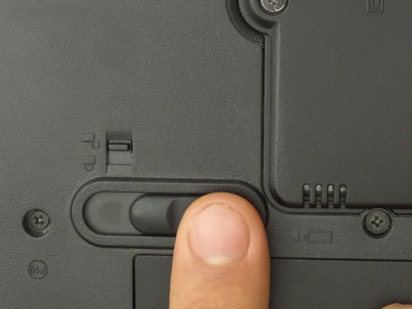 Use any finger to move the larger switch above the battery to the left and hold the switch.