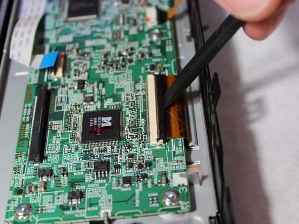 Flip up the black clasp with the spudger to disconnect the large orange ribbon cable from the main board.