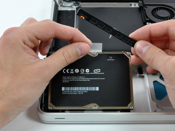 Lift the hard drive by its plastic pull tab and remove the freed hard drive bracket.