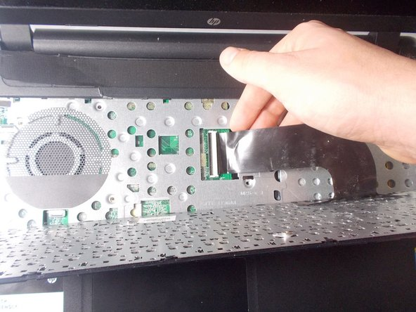 Remove the keyboard connection from the laptop by flipping up the black tab on the ZIF connector.