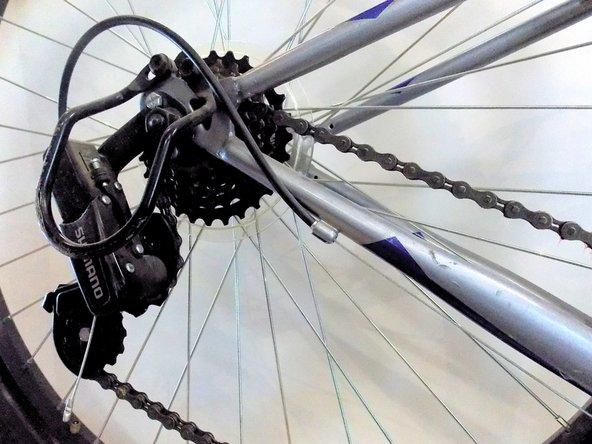 Using one hand, pull the rear derailleur forward to create slack in the chain.