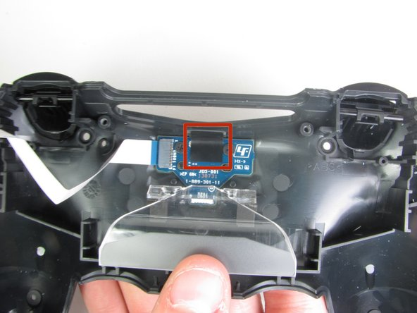With the blunt forceps remove the top part of the black tape connecting the charging port to the plastic portion of the controller.