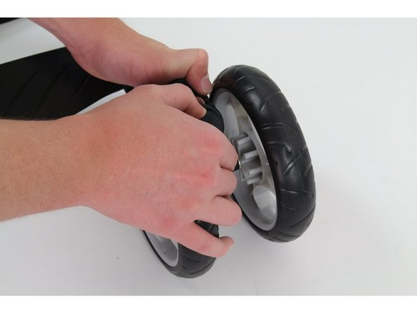 Firmly press both tabs inwards, and use your other hand to pull the wheel off