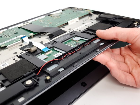 Remove the trackpad out from its housing by first sliding it towards the keyboard and then down towards the screen.