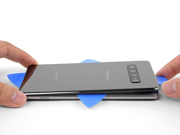 Once you have sliced around the phone, twist an opening pick in one of the edges to help separate the back cover from the frame.