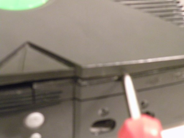 To remove the top half of the console, flip it upright and use a flathead screwdriver to separate the two halves.