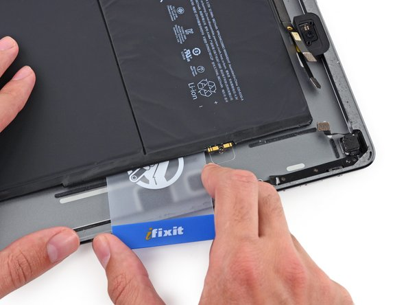 Lift the card up from the rear case slightly to allow it to pass over the battery contact mounting post.