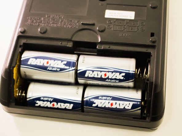 Open the battery compartment by pressing down on the small tab along the upper edge of battery cover.