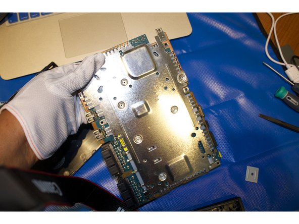 Remove the single 2.4 mm screw located on the metal casing at the top of the motherboard.