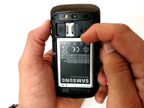 Using your index finger, pull the top of the battery. Then pull the battery towards you.