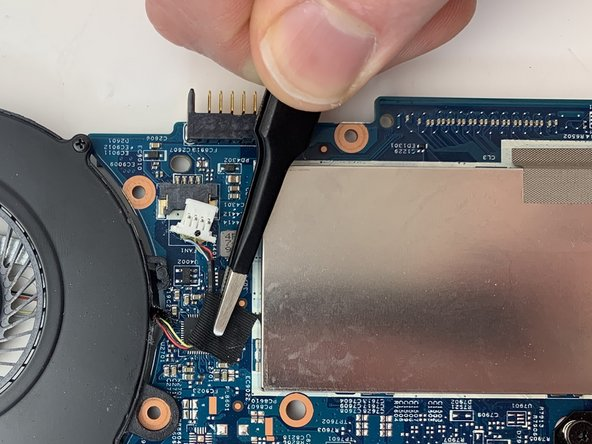 Using the Metal Tweezers, pull up the tape connecting the fan connector to the motherboard.