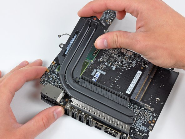 Carefully lift the heat sink off the logic board, minding the thermal sensor cable that may get caught.