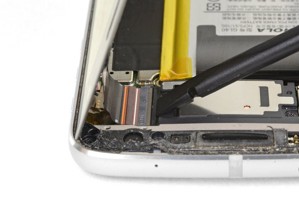 At the opposite end of the phone, use your spudger to flip open the locking tab on the display cable connector.