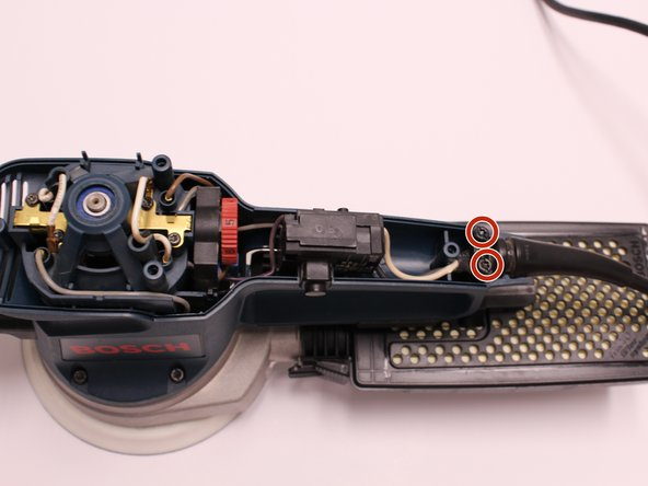 Using the T20 Torx Screwdriver, remove the two 15.6 mm screws securing the cable clip  to the motor housing.