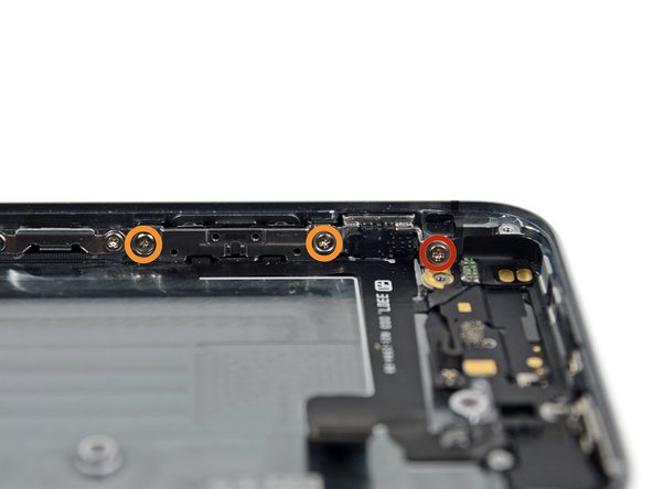 Remove the following screws securing the volume button and ringer switch brackets to the side of the rear case: