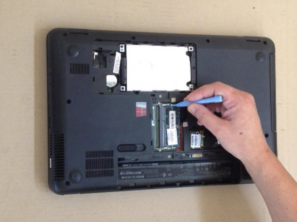 Use a plastic tool to open lockers of the memory module.