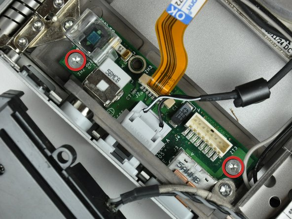 Remove the two T8 Torx screws securing the DC-in board to the lower case.