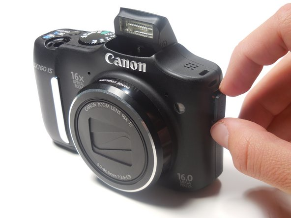 Use your finger or a spudger to gently pry the battery tray out of the camera.