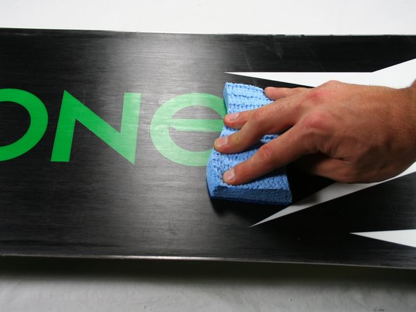 Brush the wax using the Scotch Brite Pad to add small grooves. Use long brush strokes starting at the tip of the snowboard and ending at the tail.