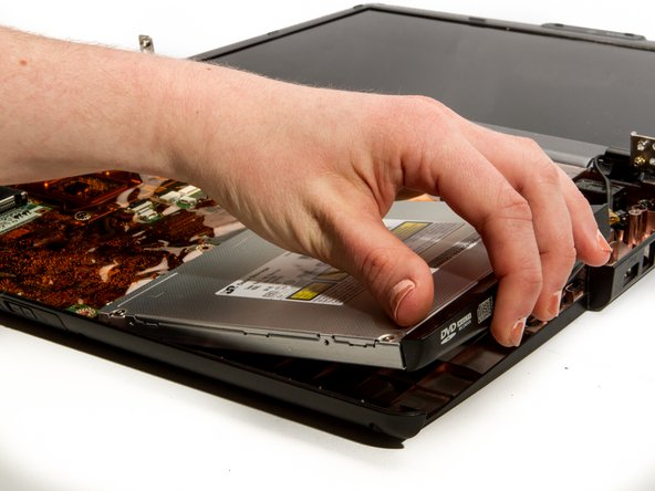Gently lift the disk drive by its outward facing edge (the one with writing on it).