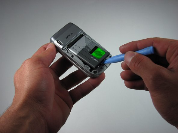 Insert the iPod opening tool between the base of the phone and the phone battery.
