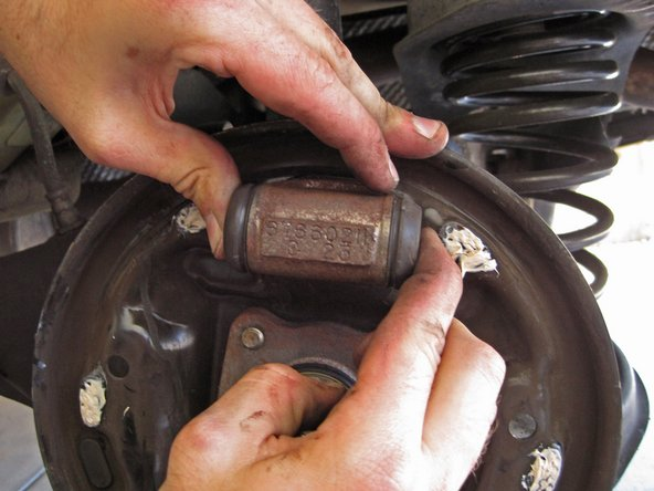 Use your hands to compress the pistons of the brake cylinder.