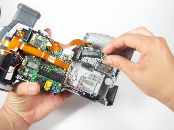 """Remove the circuit board you just unscrewed. It is the black rectangle that says """"CAUTION"""" on it."""