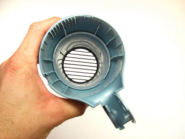 Once you have removed the inner parts of the dryer head, you can just pull out the front grill piece and replace it with a new one.