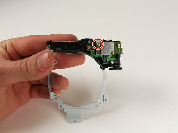 Grab the metal frame with the flash assembly that was removed from around the lens assembly.