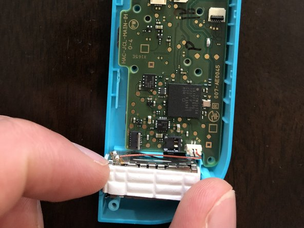 Carefully remove the rumble pack connected to the motherboard by gently lifting it out of its casing.