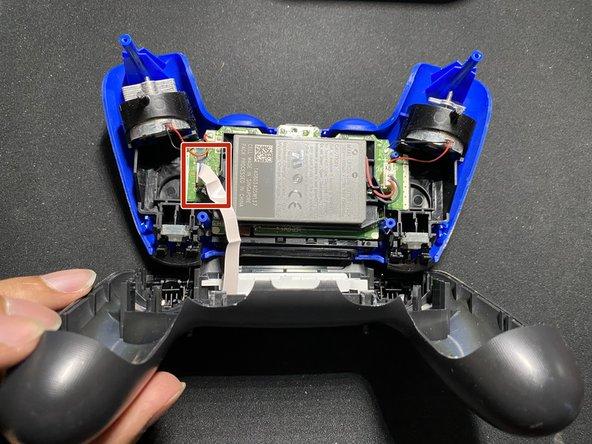 Löse das Flachbandkabel, um das Touchpad von der Hauptplatine des Controllers zu trennen.