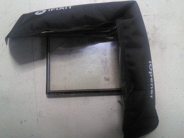 Chauffez les contours du tactile pour le décoller plus facilement puis poussez le doucement par dessous avec les doigts pour l'extraire.