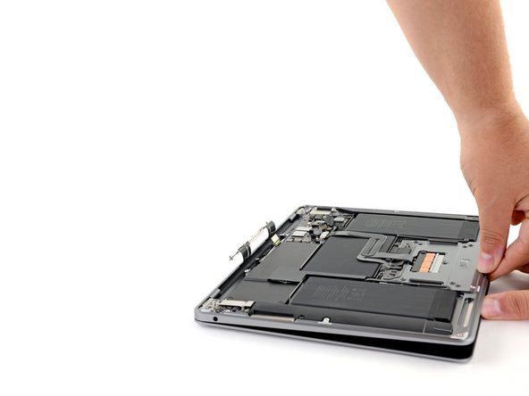 With the MacBook still screen-side down, carefully lift the upper case to open the MacBook as far as possible.
