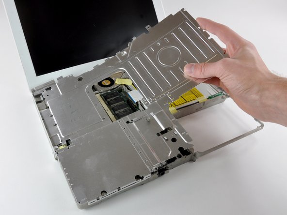 Lift the top shield up from the right side, minding the upper left corner, which may catch on the metal framework.