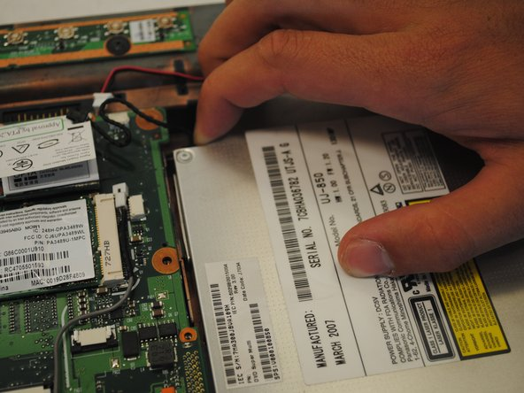 Using two fingers, slide the optical drive toward the edge of the computer.