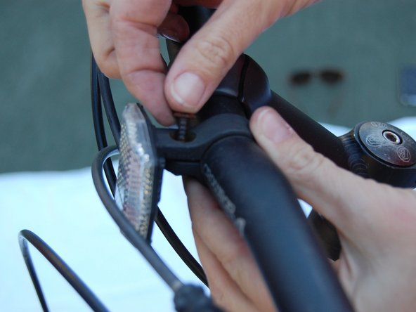 Remove the screw. Bracket should now be able to rotate freely around the handlebar.