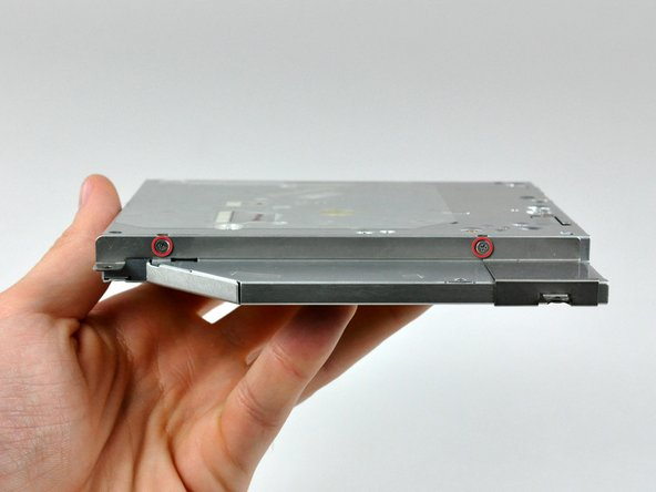 Remove the two Phillips screws holding the optical drive bracket to the side of the optical drive.